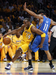 Los Angeles Lakers Bryant drives around Orlando Magic's Lee during Game 1 of their NBA Finals basketball game in Los Angeles