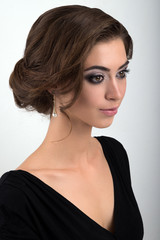 Close-up portrait of brunette with evening makeup and collected hair in a black dress standing half-turn on a light background