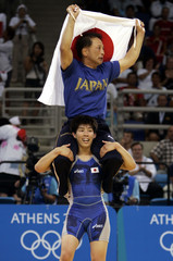 Japan's Yoshida celebrates with coach her gold medal after women's freestyle wrestling at the Athens ...