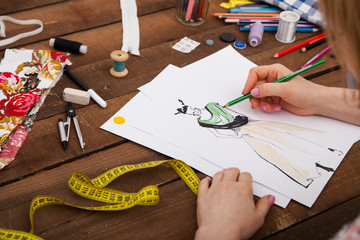 Fashion designer drawing new models of clothes
