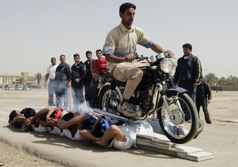 A policeman drives a motorcycle over police graduates as they demonstrate their skills during a graduation ceremony in Baghdad
