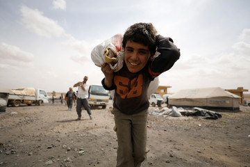 An internally displaced Syrian boy who fled Raqqa city, reacts while carrying a bag on his back inside a camp in Ain Issa