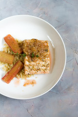 Grilled salmon with quinoa and rhubarb sauce. Gray background, white plate. Isolated.