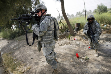 """U.S. soldiers from the 2nd battalion, 32nd Field Artillery brigade take up positions during a chase for a """"high priority target"""" in Baghdad"""