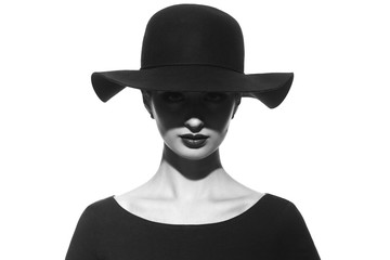 Black and white fashion portrait of a silhouette of a girl in a hat with wide brim with a shadow in front of her eyes.