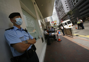 A police officer stands guard outside a hotel in which approximately 200 guests and 100 staff are ordered to stay in Hong Kong