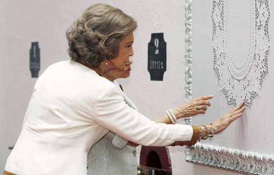 Spanish Queen Sofia and Maria Cavaco Silva, wife of Portugal's President, touch Madeira needlework during visit on Atlantic island of Madeira
