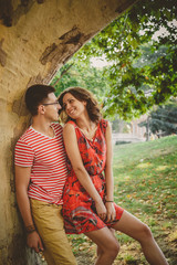 Smiling couple in red clothes in love outdoors under a big tree looking at each other. Focus on man