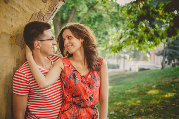 Beautiful happy loving couple in red clothes on nature under a big tree embracing and looking at each other
