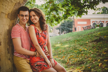 Beautiful happy loving couple in red clothes on nature under a big tree embracing
