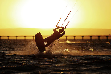 Kiteboarding sportsman silhouette, sunset in the sea