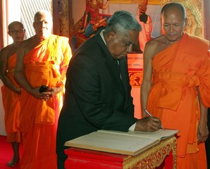 Singaporean President Nathan is flanked by Thai Buddhist monks as he signs visitors book during ...