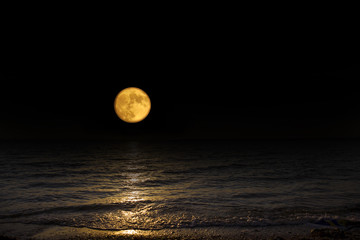 Full moon over the sea. Astronomy shot of the planets and the starry sky. The scene with the round moon. The mystical nature time.