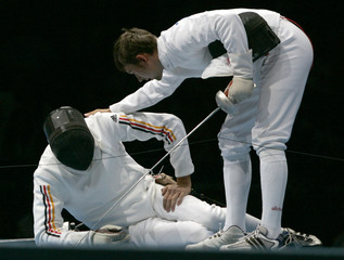 Russia's Tourchine leans over Germany's Schmid during bronze medal match in men's fencing team epee ...