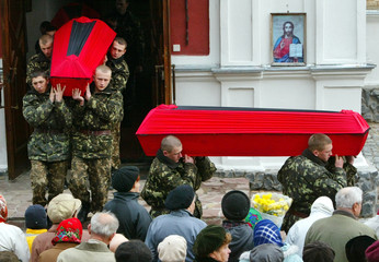 Ukrainian soldiers carry coffins containing the remains of Red Army soldiers, who died in World War II, in Vyshgorod