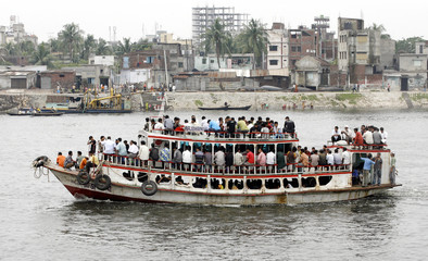 A ferry carries office workers on the river Buriganga in Dhaka