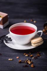 Fruit tea and coffee creme macaron on dark wooden background