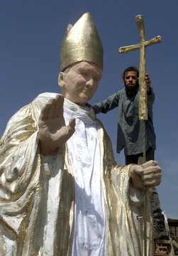 A cross is fitted at a work shop on March 15, to a costume figure of Pope John Paul that will march ..