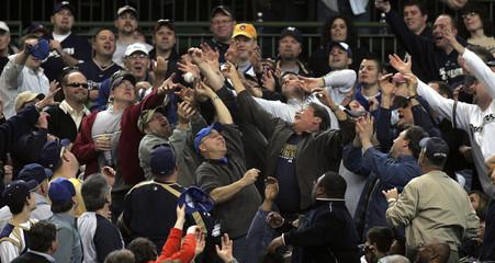 Baseball fans reach for a foul ball hit by Milwaukee Brewers batter Ryan Braun in Milwaukee
