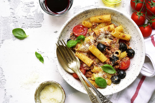 Tortiglioni bolognese with tomato cherry and black olives.Top view.