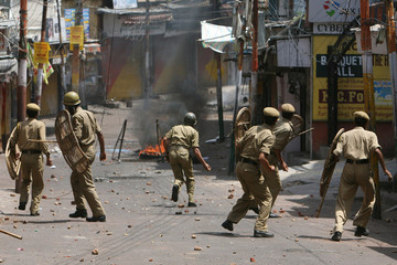 Indian policemen throw stones back at demonstrators during a protest in Jammu