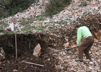A man digs out stones, which will later be sold for money, in Torovica