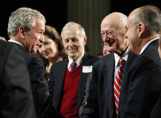 U.S. President George W. Bush speaks with former New York City Mayors Ed Koch and Rudy Giuliani after making remarks on financial markets and the world economy at the Federal Hall National Memorial in New York