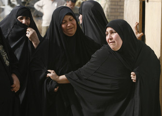 Women grieve as they wait to claim the body of a relative who was killed in a suicide bomb attack in Baghdad