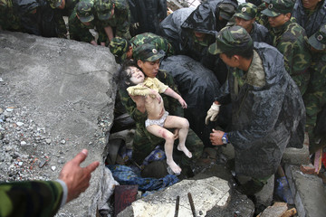 Soldiers rescue a child from the rubble after an earthquake in Beichuan,
