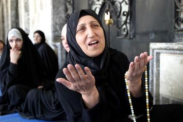 An Iraqi muslim woman prays at the Abdel-Kader al-Guilani mosque in Baghdad, May 2,2003. [Iraqi poli..