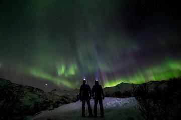 Foto op Aluminium Noorderlicht couple looking the northern lights in the wild