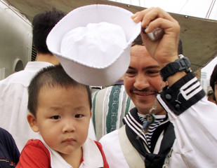MEXICAN SAILOR PUTS CAP ON A YOUNG CHINESE VISITOR IN SHANGHAI.