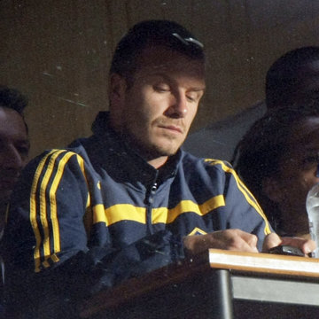 David Beckham types a text message on his mobile phone in the Chairman's box in Wellington