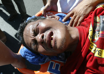A DEVOTEE GRIMACES ON HIS WAY TO THE HOSPITAL AFTER HE WAS TRAMPLED DURING THE ANNUAL BLACK ...