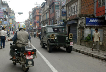 An army vehicle passes through a street in the capital Kathmandu after curfew was briefly relaxed.