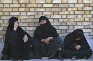 Iraqi women grieve at the funeral for 22 men found slain in eastern Iraq
