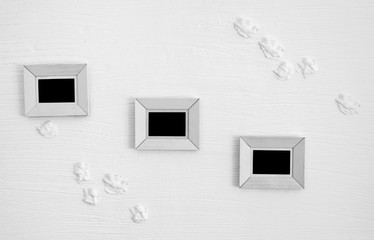 Three white wooden photo frames on the wall