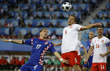 Poland's Dudka heads ball over Croatia's Klasnic during their Euro 2008 soccer match in Klagenfurt
