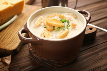 Delicious beer cheese soup with croutons and onions on table