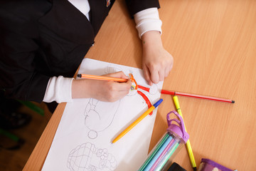 Child draws felt-tip pens. Small child holds a blue felt-tip pen in hand and draws abstract princesses castle. A kids drawing, a set of colored felt pens on a wooden table. Kindergarten art background