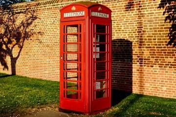 Cabine téléphonique rouge et mur en brique