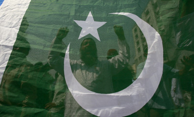 Activists of Pakistan's Islamist party Jamaat-e-Islami chant slogans behind a flag during countrywide anti-government protest rally in Karachi