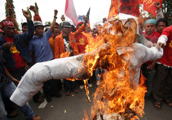 Workers burn an effigy of US President George W. Bush during a May Day rally in Makassar