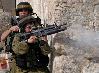 Israeli soldier fires tear gas grenade at Palestinian protesters during clashes in West Bank village ...