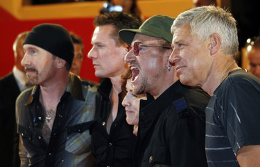 """Irish director Catherine Owens and U2 band members arrive for a gala screening of """"U2 3D"""" at the Cannes Film Festival"""