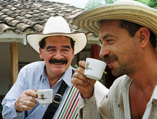 COLOMBIAN COFFEE ICON JUAN VALDEZ SHARES A CUP OF COFFEE WITH A FRIEND.