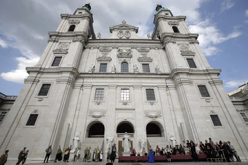 Actors perform on stage in front of Salzburger Dom cathedral