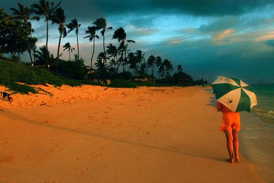 WOMAN WALKS ALONG SHORE OF HAWAIIAN BEACH.