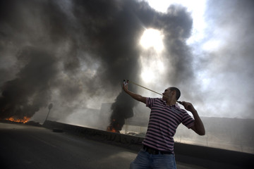 Palestinian protester uses a slingshot to hurl stones at Israeli soldiers during clashes at Qalandiya checkpoint