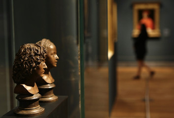 "A woman walks past busts titled  ""Cabeza de hombre y muchacha"" by German artist Michael Erhart in Madrid"